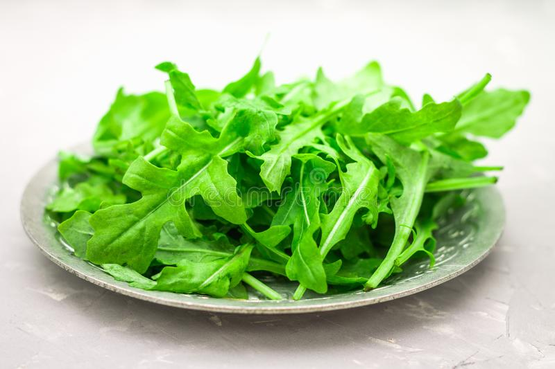Fresh juicy leaves of arugula on a light concrete background. royalty free stock images