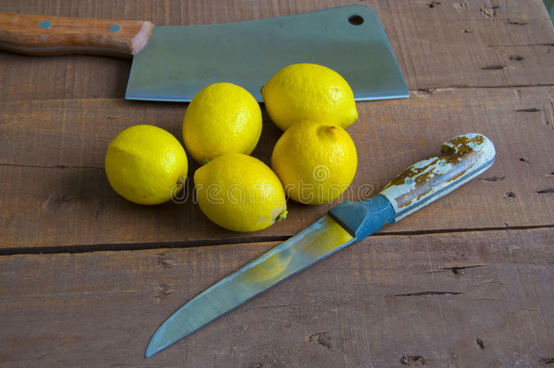 Fresh juicy lemon on top of the salad and fresh for the fish. Knife and lemon pictures ready to cut on the table,Fresh juicy lemon on top of the salad and fresh stock image