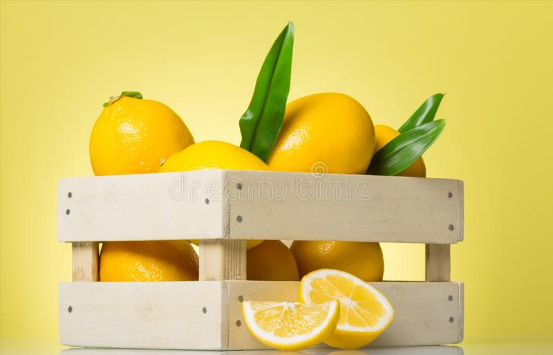 Fresh juicy lemons in a wooden box on yellow stock images