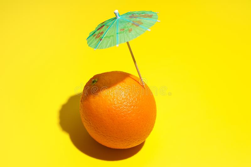 Fresh juicy orange with a cocktail umbrella isolated on yellow background. Concept of Healthy eating and dieting. Drink concept stock photo