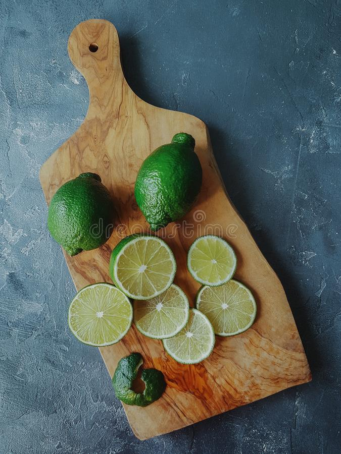 Fresh juicy organic lime in slices on wooden board and dark stone background. Ripe fruit, healthy lifestyle, top view, selective f stock images