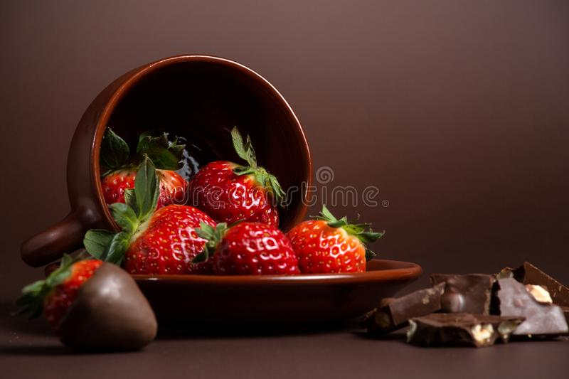 Fresh juicy organic strawberries in an old clay bowl on a brown background stock image