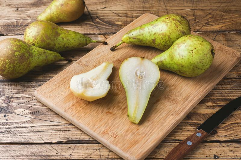 Fresh juicy Pears Conference whole and cut by slides on wooden rustic background royalty free stock images