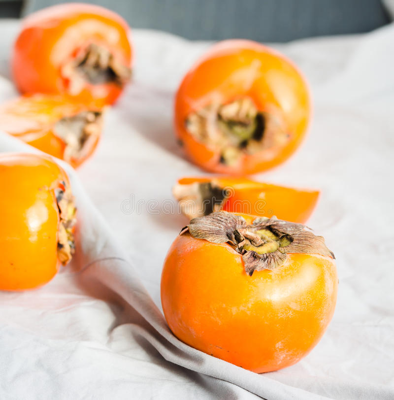 Fresh juicy persimmons on a light background, raw fruit royalty free stock images