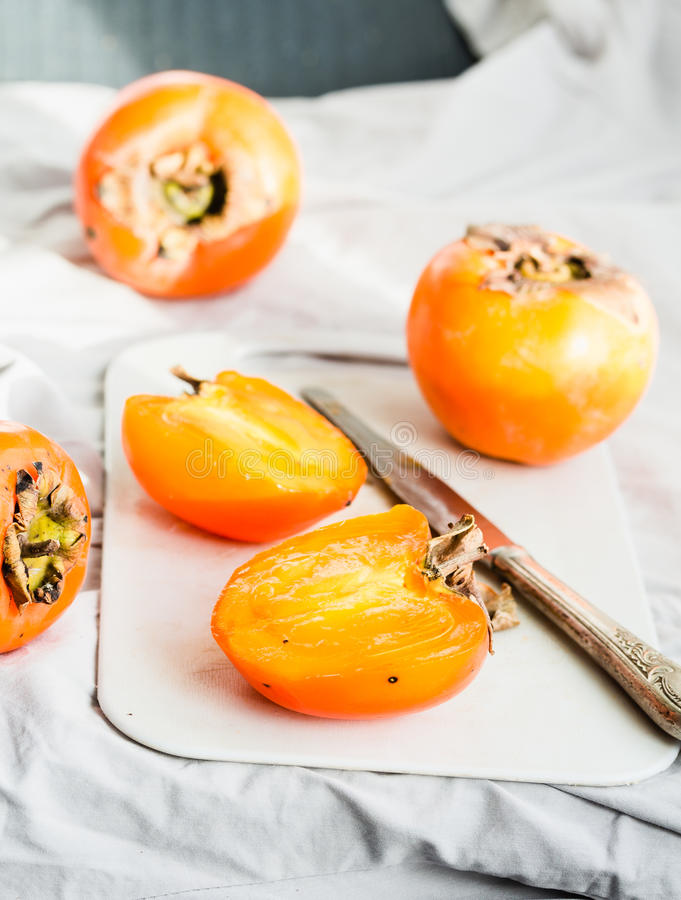 Fresh juicy persimmons on a light background, raw fruit royalty free stock photo