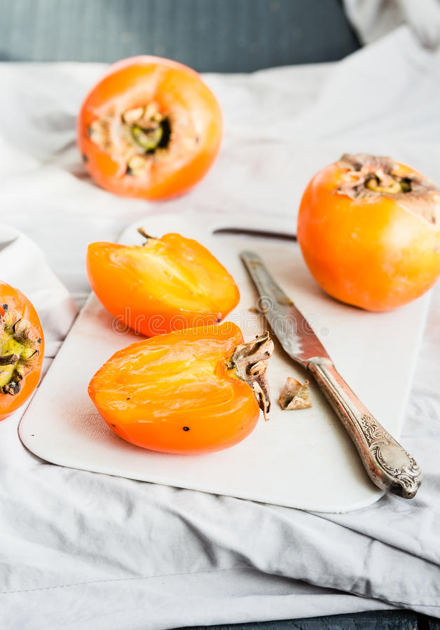 Fresh juicy persimmons on a light background, raw fruit stock photography