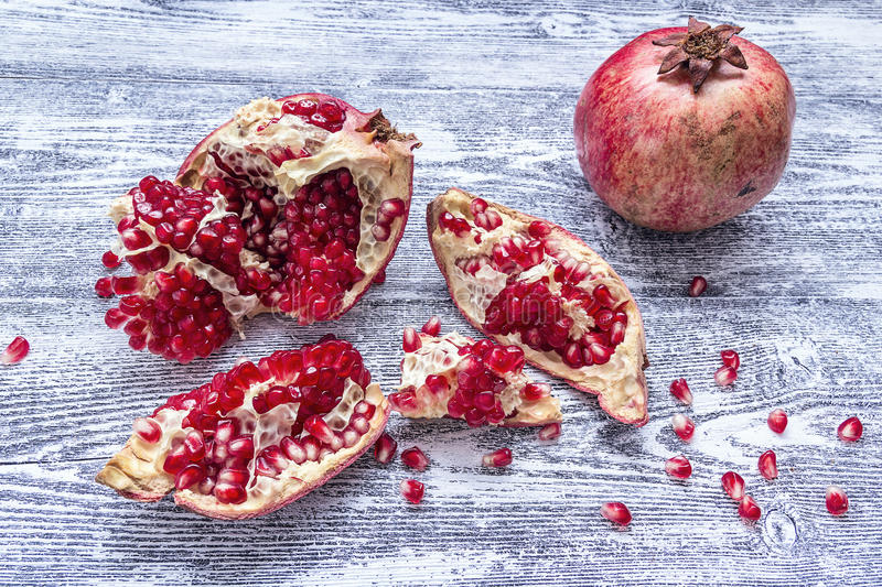 Fresh juicy pomegranate - whole and cut on a wooden grey background. stock images