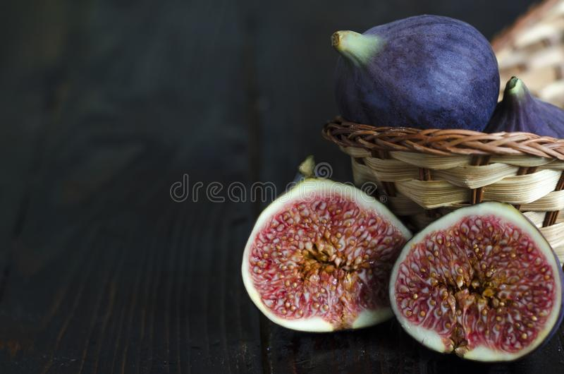 Fresh juicy ripe blue figs with small bones, exotic and tropical fruit in a basket on dark wooden background. low key, copy space. Fresh juicy ripe blue figs royalty free stock photography