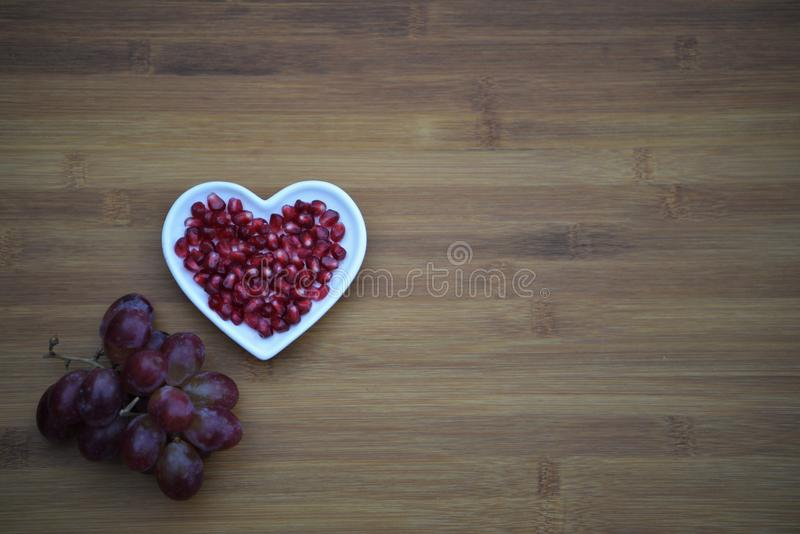 Food photography image of healthy red pomegranate seeds in a white love heart shape dish with purple grapes on wood background royalty free stock photos