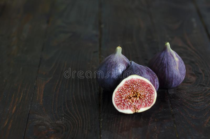 Fresh, juicy, ripe, sweet figs with small bones on a dark wooden background. low key, copy space, mock up. Text stock photo