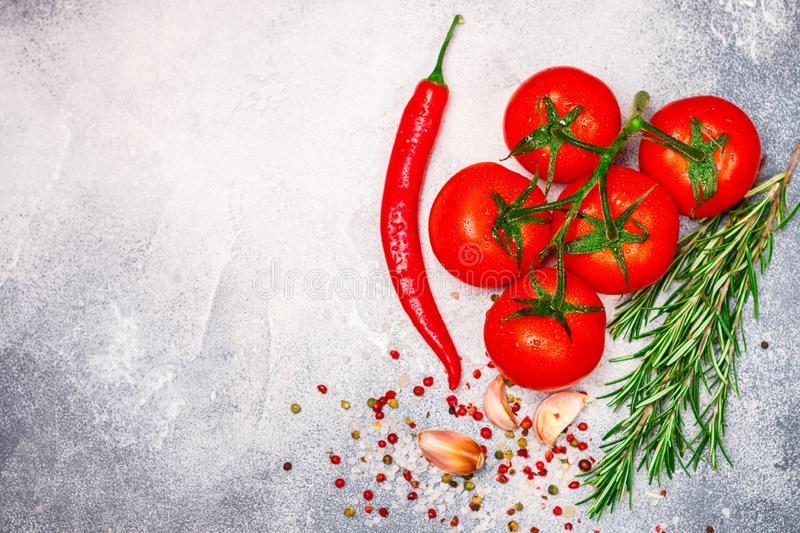 Fresh juicy ripe tomatoes on a branch, red pepper, rosemary, garlic and spices royalty free stock photos