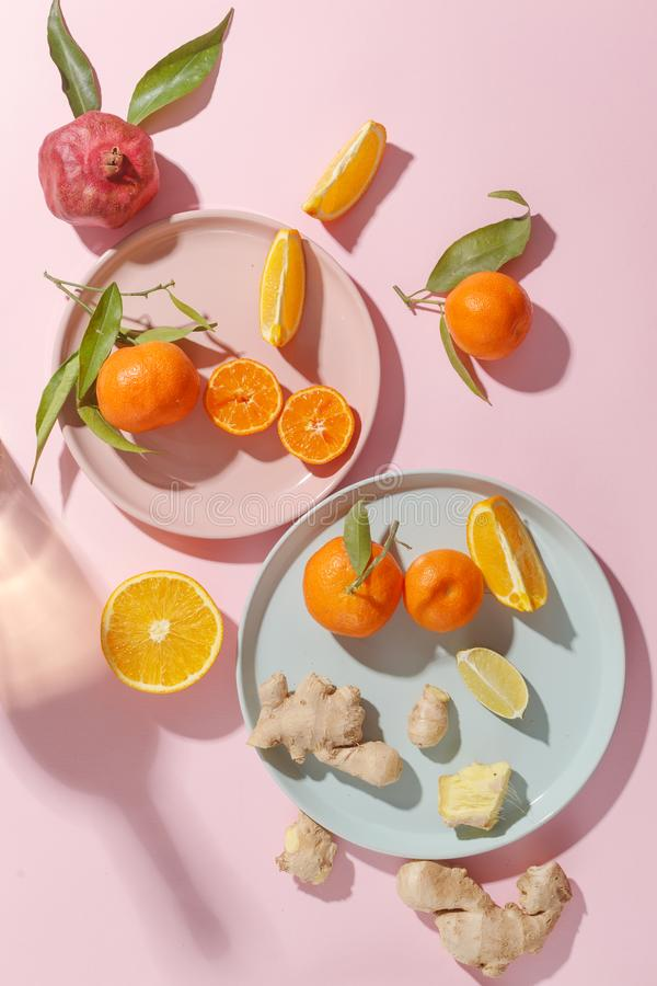 Fresh juicy tangerines, pomegranates and sliced fruits on colored plates on a pink background. Summer mood, healthy food. Top view stock images