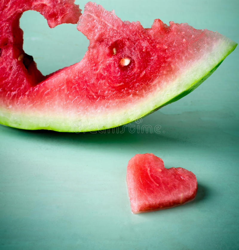 Fresh juicy watermelon heart at turquoise wooden background. Saint Valentine, love greeting card royalty free stock photo