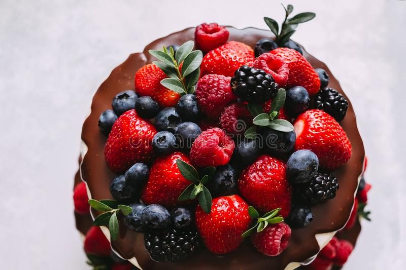 Fresh and juicy wedding cake. Fresh and juicy forest berries of blackberry, raspberries, blueberries, strawberries decorate the chocolate wedding cake royalty free stock photography