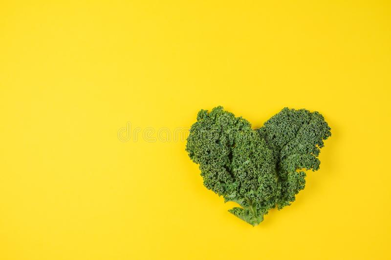 Fresh kale leaves in the shape of a heart on yellow background. stock photos