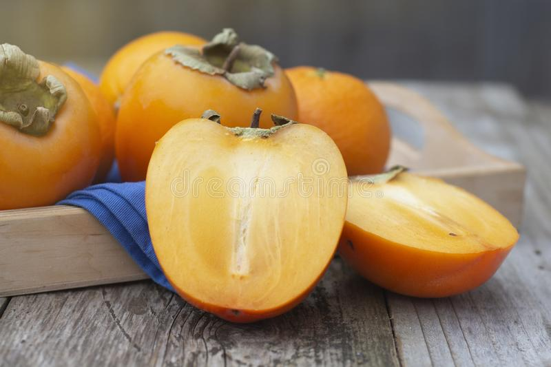 fresh khaki fruit isolated, sliced in half, on rustic table. Healthy food stock photography