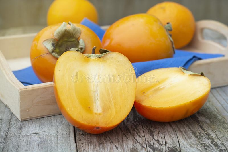 fresh khaki fruit , sliced in half, on rustic table. Healthy food royalty free stock photography