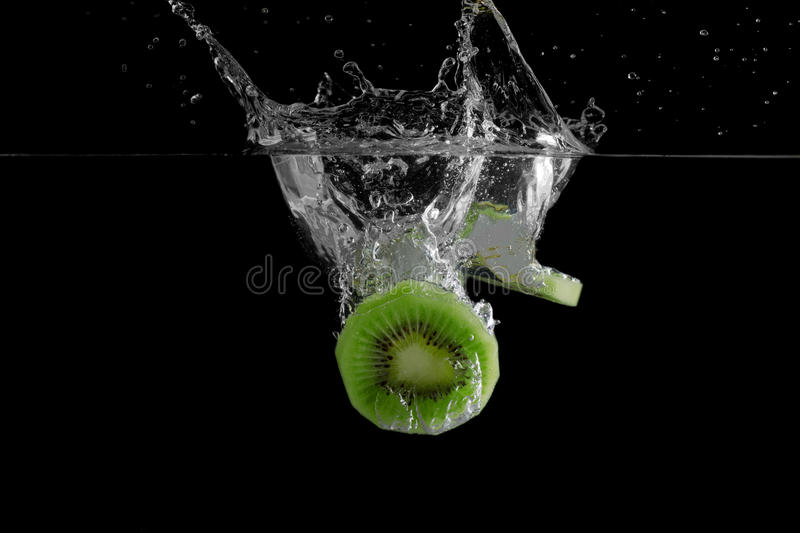 Fresh Kiwi Fruit. Falling into water stock photo