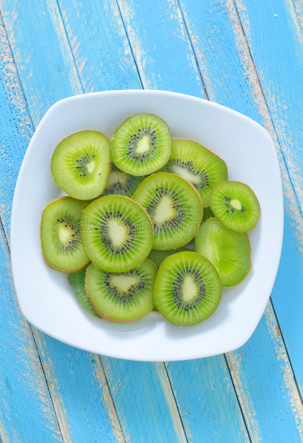 Fresh kiwi. On white plate royalty free stock photo