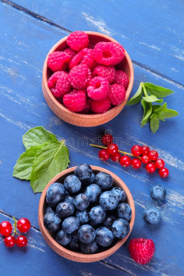 Fresh, large blueberries and raspberries in a wooden bowl close-up with mint stamens on a blue wooden background. royalty free stock photography