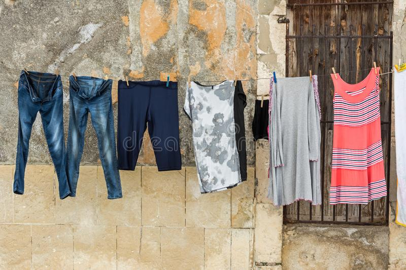 Fresh laundry drying on clothes line in front of Mediterranean town house wall. Fresh laundry drying on clothes line in front of weathered Mediterranean town royalty free stock photography