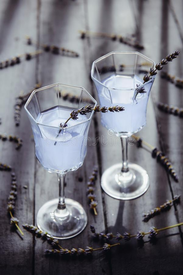 Fresh lavender lemonade with flowers in beautiful glasses on dark wooden table in back light. Detox water. Summer drink. Diet. Cocktail. Selective focus. Copy stock images