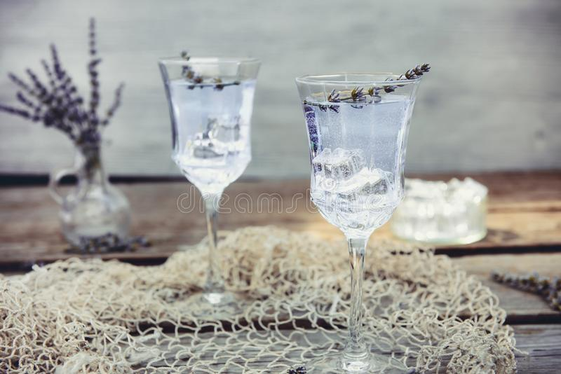 Fresh lavender lemonade with flowers and ice cubes in beautiful glasses on rustic wooden table. Detox water. Summer drink. Diet. Cocktail. Selective focus. Copy royalty free stock images