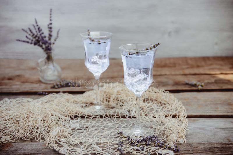 Fresh lavender lemonade with flowers and ice cubes in beautiful glasses on rustic wooden table. Detox water. Summer drink. Diet. Cocktail. Selective focus. Copy royalty free stock photo