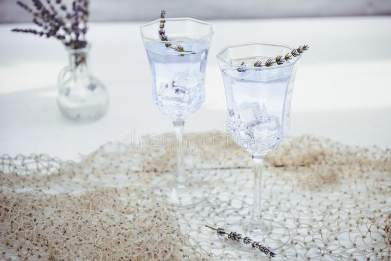 Fresh lavender lemonade with flowers and ice cubes in beautiful glasses on white wooden table. Detox water. Summer drink. Diet. Cocktail. Selective focus. Copy royalty free stock photography