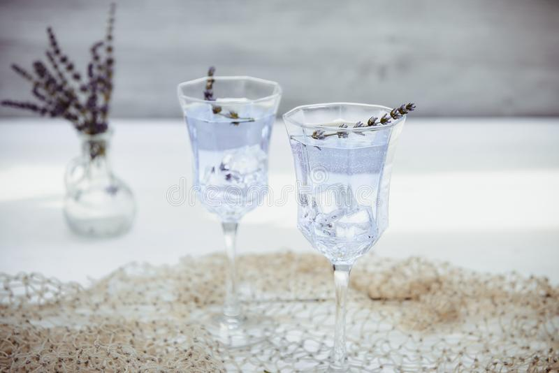 Fresh lavender lemonade with flowers and ice cubes in beautiful glasses on white wooden table. Detox water. Summer drink. Diet. Cocktail. Selective focus. Copy royalty free stock photo
