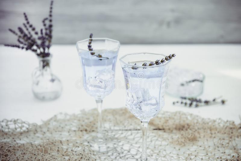 Fresh lavender lemonade with flowers and ice cubes in beautiful glasses on white wooden table. Detox water. Summer drink. Diet. Cocktail. Selective focus. Copy royalty free stock image