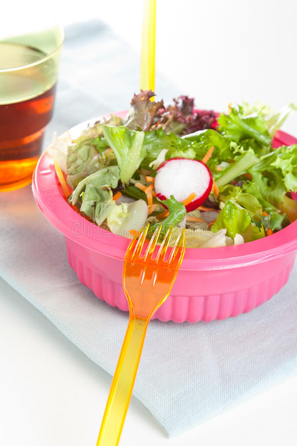 Fresh leafy green salad. In a pink bowl with plastic disposable cutlery stock images
