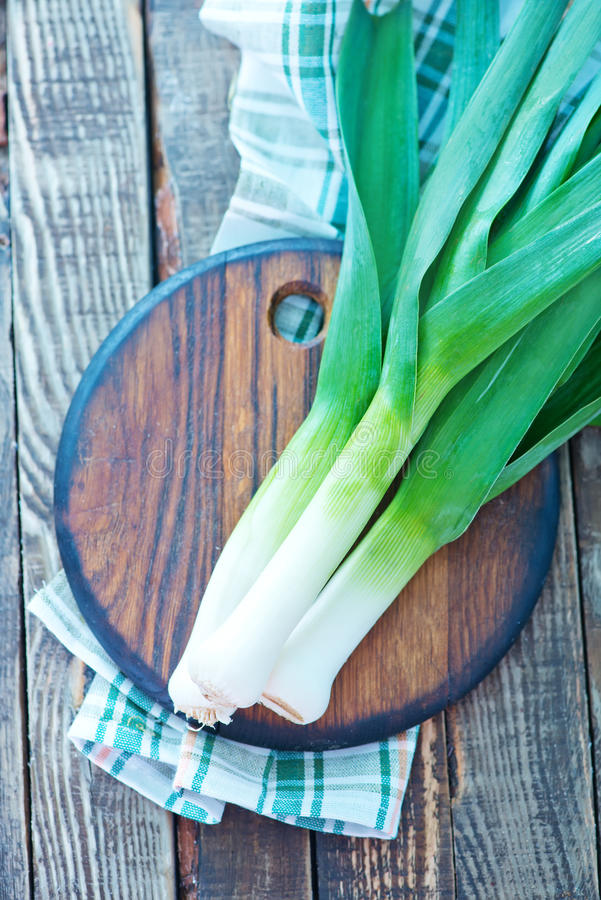 Fresh leek. On wooden board and on a table royalty free stock photography