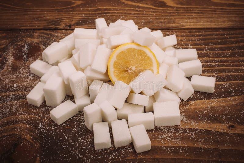 Fresh lemon on bunch of sugar cubes and granulated sugar stock photography