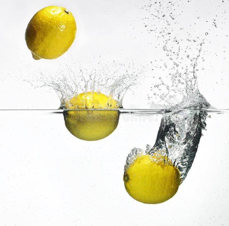 Fresh Lemon Dropped Into Water Stock Image