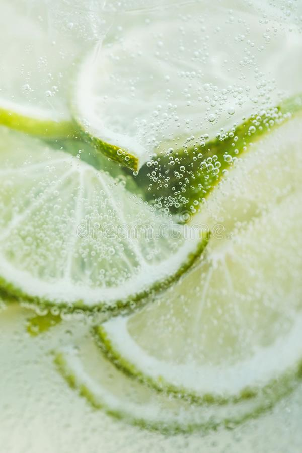 Fresh lemon slices in cold lemonade with bubbles. Close-up fresh lemon slices in cold lemonade with bubbles. Summer tropical beverage stock photo