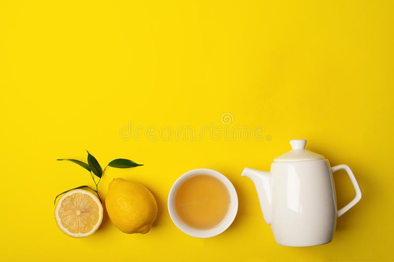 Fresh lemon tea or detox drink in a white cup and a teapot on a bright yellow background. Healthy eating concept. Horizontal frame. Copy space. Flat Layout Top stock photography