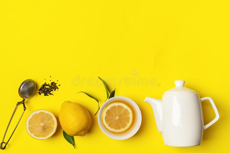 Fresh lemon tea or detox drink in a white cup and a teapot on a bright yellow background. Healthy eating concept. Horizontal frame. Copy space. Flat Layout Top royalty free stock photos