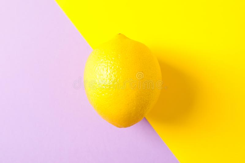 Fresh lemon on two tone background. Space for text royalty free stock photo