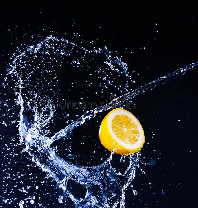 Lemon into water splash on black background. Fresh Lemon into water splash on black background stock image