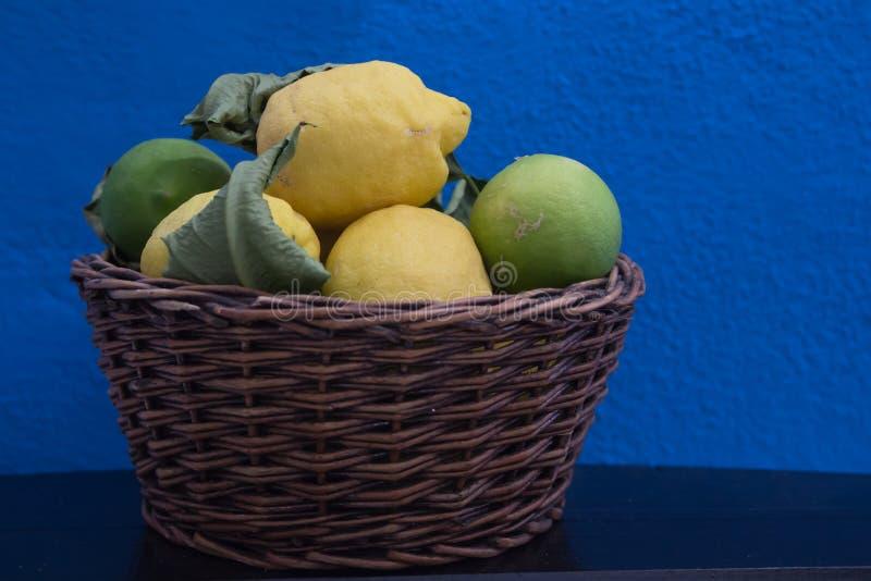 Fresh lemon in a wicker basket on a blue background royalty free stock photo