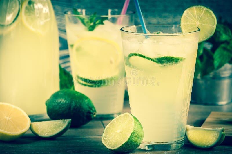 Fresh lemonade drink. Refreshing lemonade drink and ripe fruits against wooden background stock photos