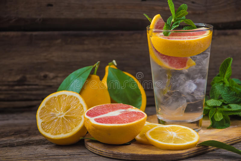 Fresh lemonade in a glass beaker with ice, green mint, red orange and lemon on the wooden table royalty free stock photos
