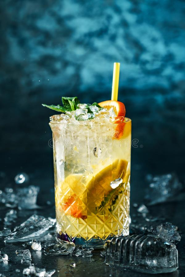 Fresh lemonade with mint, ginger, orange and ice in glass jar on the dark blue background. Summer cold drink and cocktail stock photography