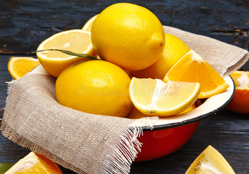 Fresh lemons and oranges in an old plate with linen napkin. Dark blue background royalty free stock image