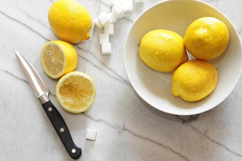 Fresh lemons and sugar cubes on marble counter. Top royalty free stock image
