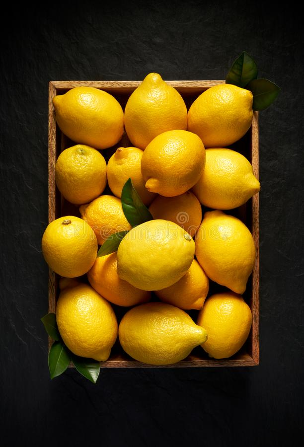 Fresh lemons in a wooden container on a black stone background, top view. stock photo
