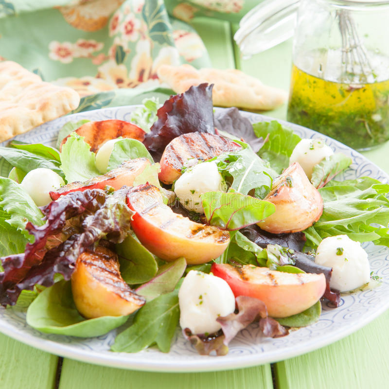 Fresh lettuce with grilled peaches. And mozzarella balls royalty free stock image