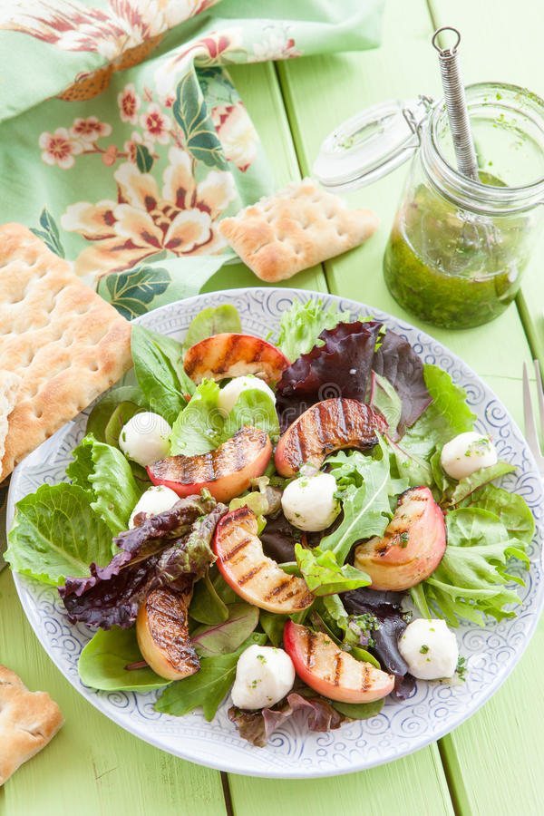 Fresh lettuce with grilled peaches. And mozzarella balls stock image