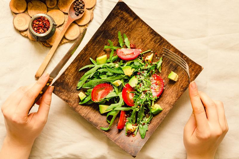 Fresh light green salad with avocado and tomatoes in a wooden plate. Top view. The process of eating. Hands of a young woman stock images